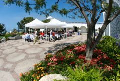 People eating at tables under white tents in the Courtyard