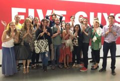 A group picture of young adults standing outside Five Guys restaurant during convocation