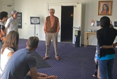 Brother Satyananda standing in the Foyer talking with young adults during a young adult retreat